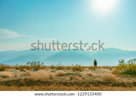 Young man exploring Death Valley National Park, California, hiking down the desert and dunes in Death Valley, California. Handsome boy alone in the middle of the desert. Small people, big world.