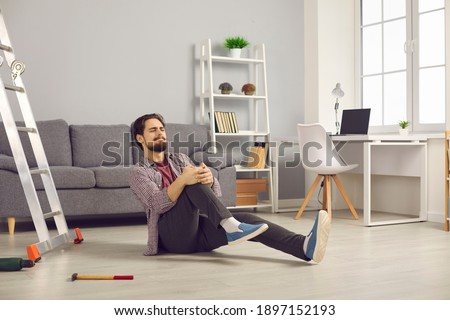 Young man fallen from ladder sitting on floor and suffering from awful pain. Unlucky guy fell off ladder while doing home repairs and hurt his knee. Concept of dangerous domestic accidents Stock photo ©
