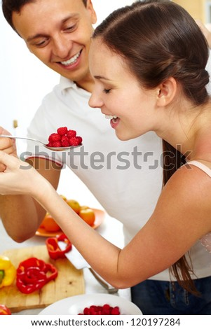 Young man feeding happy woman with ripe raspberry