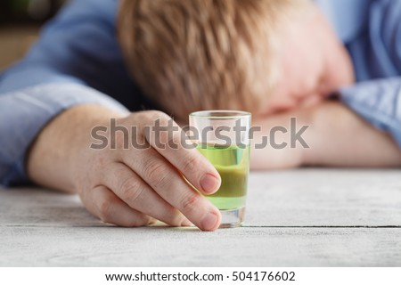 Young man feeling alone and drinking too much alcohol in his own home at the table #504176602