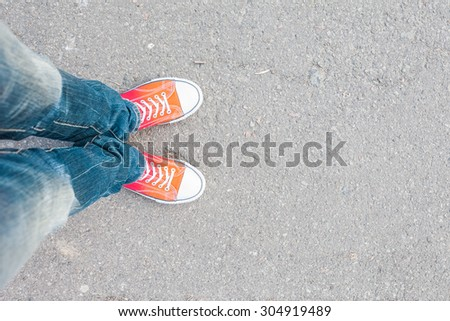 young man feet in red sneakers...