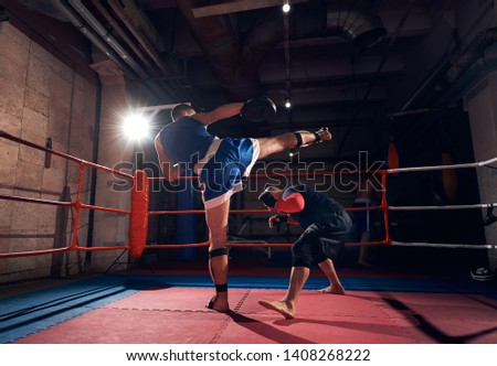 young man fighter training mma with his trainer, fighting in the ring at the health club