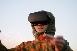 young man, firefighter with VR headset and in a green protective jacket with hood enjoying augmented reality and being trained not to be afraid of fire