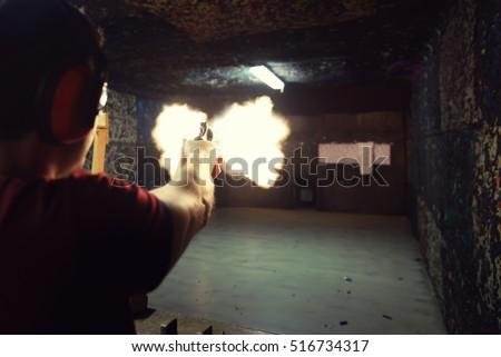 young man firing a gun at a...