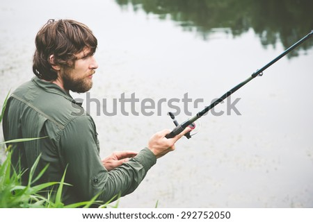 Young Man Fisherman bearded fishing with rod Lifestyle Travel survival concept river on background