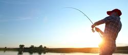 Young man fishing at sunset