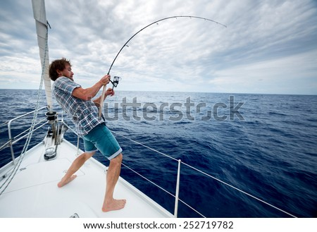 Young man fishing in open sea from sail boat #252719782
