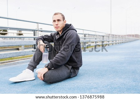 Young man fitness trainer in a gray suit drinking water from his bottle after a fat burning morning street workout. Concept of water balance replenishment during workouts