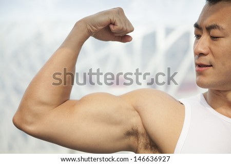 Young man flexing his bicep