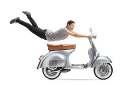Young man flying and riding a vintage scooter bike isolated on white background