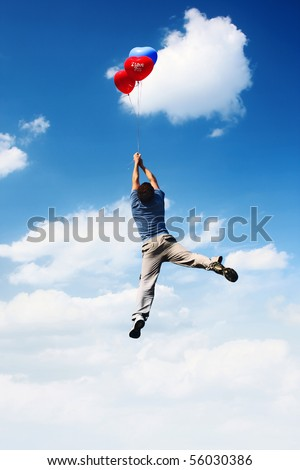 Young man flying in blue cloudy sky with colored balloons