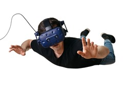 Young man flying in zero gravity space and experiencing virtual reality in 3d goggles, isolated on white background