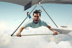 Young man flying on hang glider. Mixed media