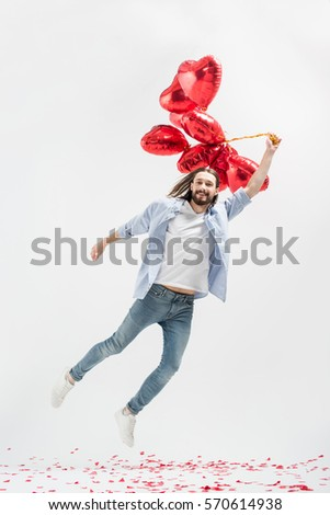 Young man flying on heart shaped air balloons isolated on grey
