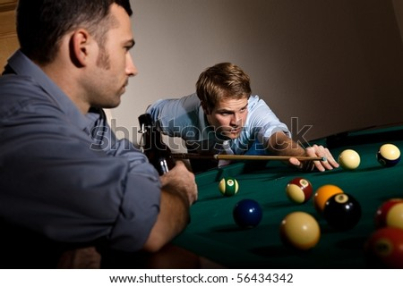 Young man focusing on playing snooker, concentrating on white ball friend watching at table.