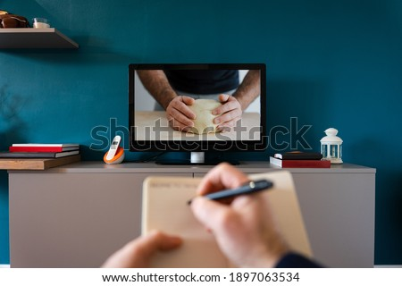 Young man follows a recipe on the TV from the sofa at home and takes notes - Video playing a cooking recipe from a blogger on his social channel - Concept of food preparation - Close up on hands Stock photo ©