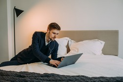 Young man freelancer lying in bed at home using laptop for work. Businessman in smart casual wear  during zoom video meeting conference call distant job. Talking by webcam in modern bedroom