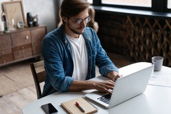 Young man freelancer using laptop studying online working from home, happy casual guy typing on notebook