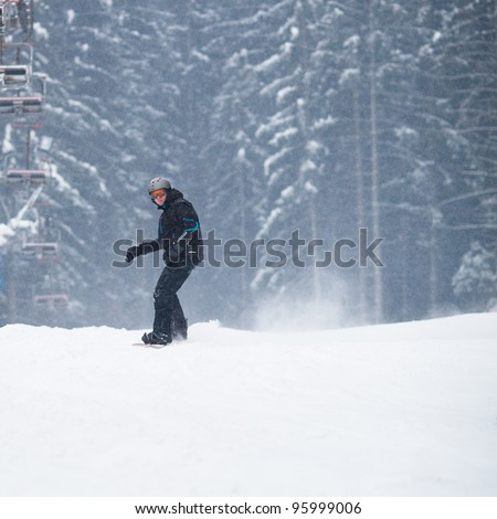 Young man freeride snowboarding off-piste in snow in a mountain resort  on a snowy winter day