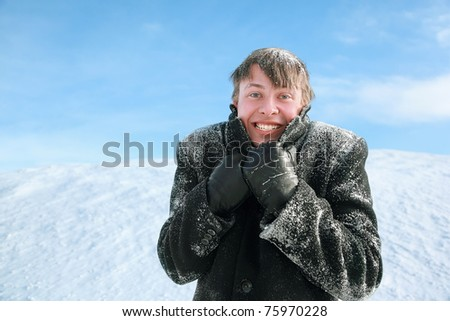 Young man froze and hides  head in collar of winter overcoat