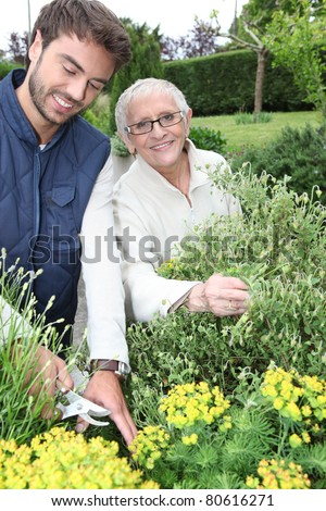 young man gardening with older woman