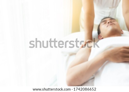 Young man get massage therapy on massage table in spa room at spa salon. Massager or massage therapist massage his shoulders. Handsome young guy get relaxing at spa room, blurred background copy space