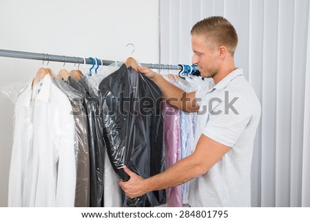 Young Man Getting Coat In Dry Cleaning Store