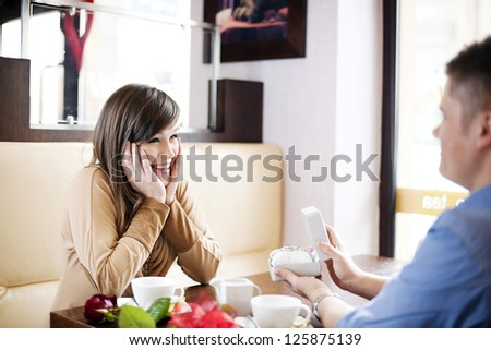 Young man giving a watch his girlfriend on Valentine's Day