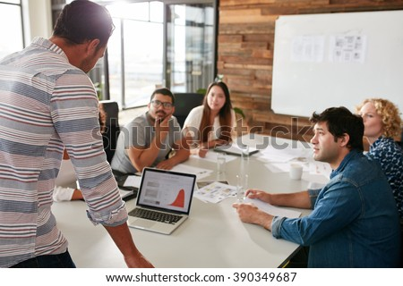 Young man giving business presentation on laptop to colleagues sitting around table in conference room.