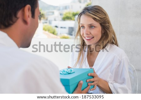 Young man giving happy woman a gift box at home