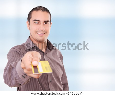 Young man giving his credit card looking at the camera,  blue background