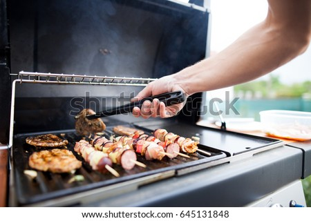 Young man grills some kind of marinated meat and vegetable on gas grill during summer time #645131848