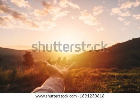 Young man hand reaching for the mountains during sunset and beautiful landscape Foto stock ©