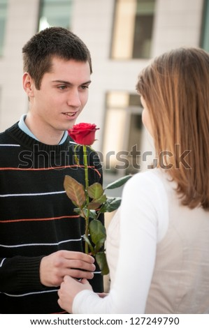 Young man handing over a flower (red rose) to woman - outdoor lifestyle scene