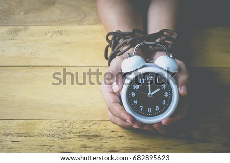 young man hands holding alarm clock while his hands bondage by old rusty metal chain lay on wooden floor, Conceptual image of freedom or bondage