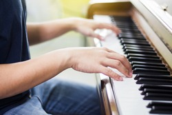 young man hands plays on piano  key