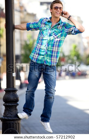Young man hanging on lamp post
