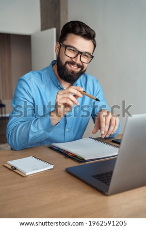 Young man happy positive smile speak to laptop camera sit at home office desk. Millennial male blogger or business coach teleconferencing. Modern technology, easy convenient online meeting concept
