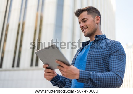 young man happy with a tablet on the street #607490000