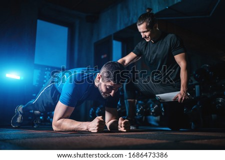 young man has workout with personal trainer in modern gym Stok fotoğraf ©