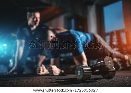 young man has workout with personal trainer in modern gym Stock photo ©