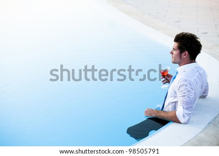 Young man having a drink in the pool, his clothes on, lots of copy-space
