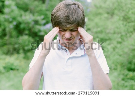 Young man having a head pain and puts his hands over the head. He is stressed