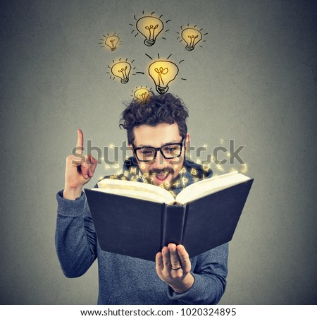 Young man having brilliant idea to come up in mind while reading smart book.