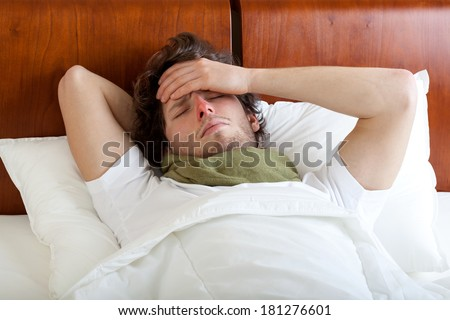 Young man having cold lying in bed, horizontal