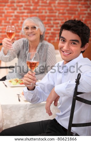 Young man having dinner with his grandmother