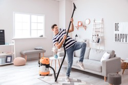 Young man having fun while cleaning floor at home