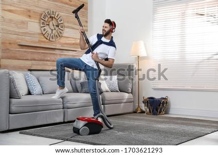 Young man having fun while vacuuming at home Stockfoto ©