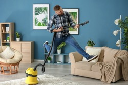 Young man having fun with vacuum cleaner while removing dirt in flat