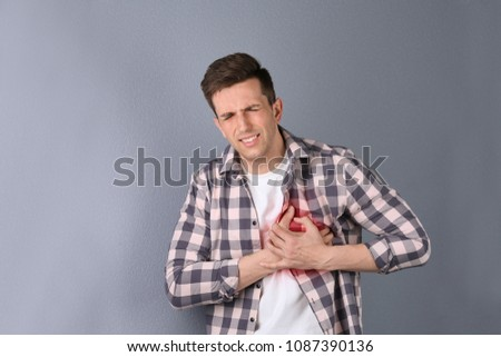 Young man having heart attack on color background